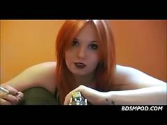 Femdom redhead smoking over a cock in chastity