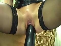 Fucking herself with a huge black dildo