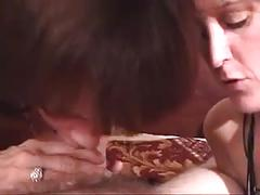 Two women suck on a cock