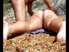 Giving her an erotic massage at the nudist beach