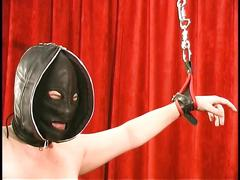 Hooded corseted chick with big tits gets shackled and caned