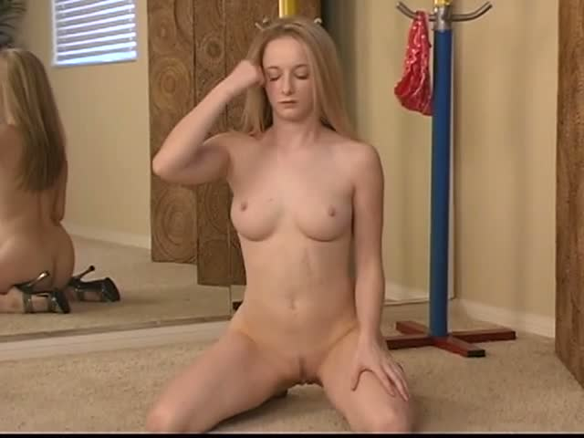 Blonde stripping while watching herself in the mirror