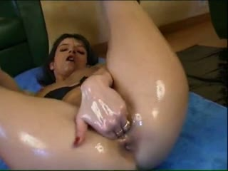 Oiled brunette masturbating and fisting