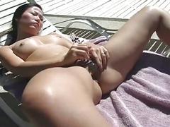 Asian slut masturbates outdoor