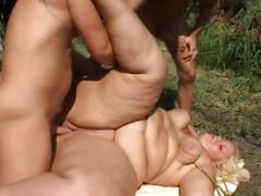 Big fat blonde takes on two hard cocks outside