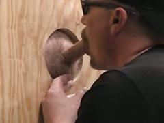 Horny bear gives blowjob through glory hole