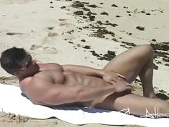 Horny hunk roughing it up on the beach