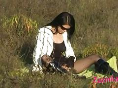 Cute brunette exposes pussy in field