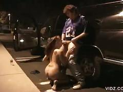 Brunette sucks his cock in a parking lot