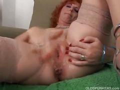 Sexy mature redhead frigs her pussy until she squirts.