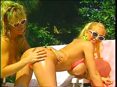 Busty blonde lesbians have sizzling poolside sex