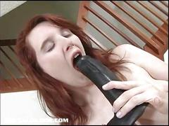 Pale redhead bounces up and down on a brutal dildo