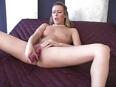 Naked girl on bed lubricates a dildo