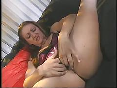 Sexy young brunette spreads legs and fingers her wet pussy on the couch