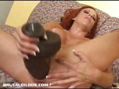 Busty redhead fills her pink pussy with huge dildo