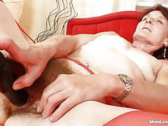 Brunette granny masturbating on her bed
