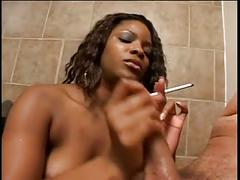 Chunky black chick smokes cigarette and gives hand job in bathroom