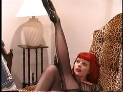 Sexy tattooed redhead in shear black stockings and heels poses for camera