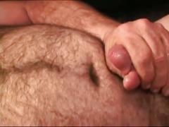 Horny bear masturbating on bed.