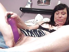 Brunette mature lady satisfying herself with a dildo