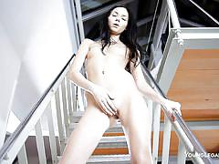 Brunette babe with long hair rubbing pussy at the stairs.
