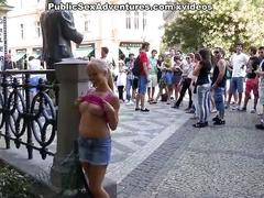 Sexy girl shows tits in the middle of a lively square