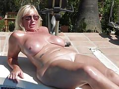 Horny mature woman masturbating by the swimming area