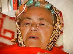 Horny granny lies on the bed and masturbates