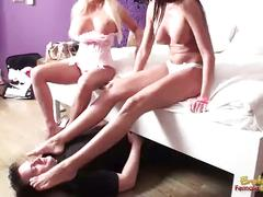 Two girls having their feet licked by a slave