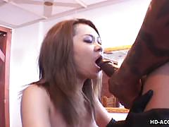 Cute asian babe gets busy with two hard cocks.