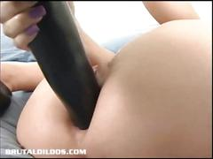 Horny brunette stuffing huge dildo.
