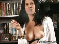 Sexy brunette smoking and showing her tits.