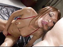 Oiled asian slut sucking a big penis.
