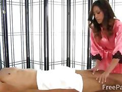 Stunning asian masseur plays with a clients big dick
