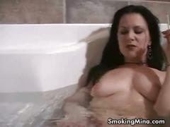 Attractive black haired babe smoking in bathtub