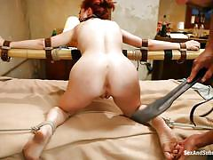 Redhead tied to the bed's frame and fucked