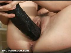 Horny brunette plays with huge black dildo