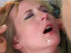 Bosomy chick tied up and sucking two cocks