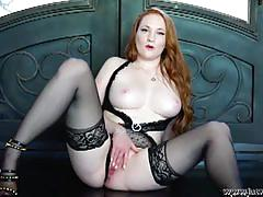 Sexy redhead in black stockings poses and plays