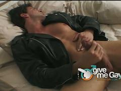Muscled hunk in leather jacket jerks off