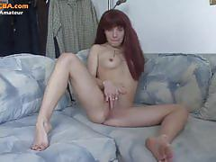 Horny red head babe finger fucks her shaved pussy.