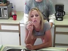 Smoking busty blonde in kitchen