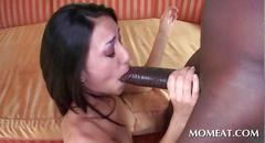 Skinny brunette blowing massive black cock