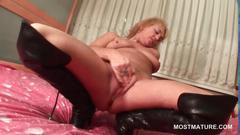 Mature blonde rubs and fingers her wet pussy