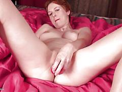 Redhead mature woman sticks vibrator in her cunt