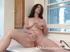 Milf kelly capone masturbates in the kitchen.