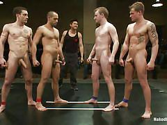 Naked men wrestle on the arena