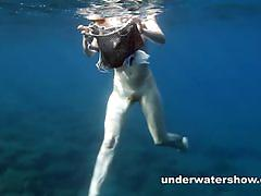 Redheaded chick gets naked under the water