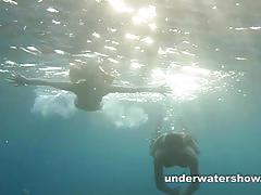 Two naughty brunette play together underwater