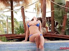 Anastasia poses wearing a blue bikini by the pool